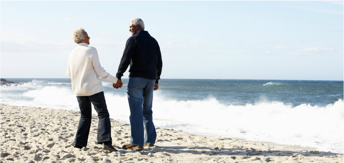 Picture of retired couple holding hands and laughing on the beach