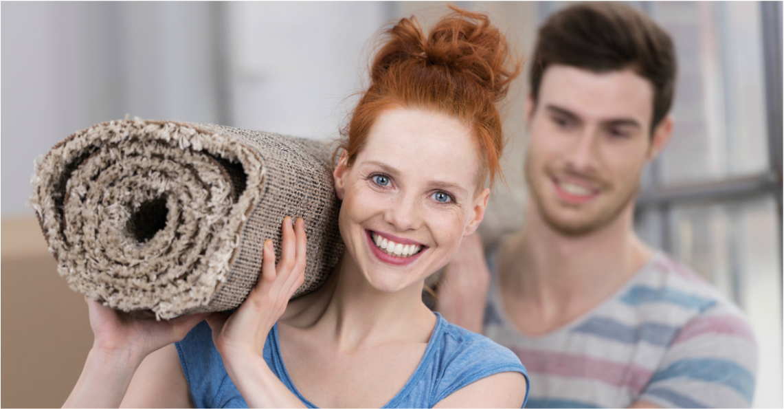 Picture  of Couple holding rolled up rug on their shoulders