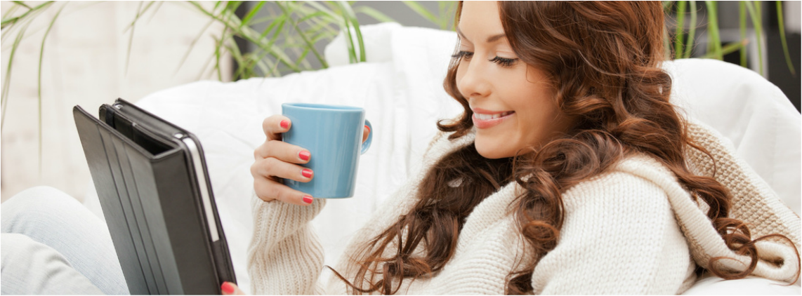 Picture of woman on couch with cup of coffee smiling at her computer