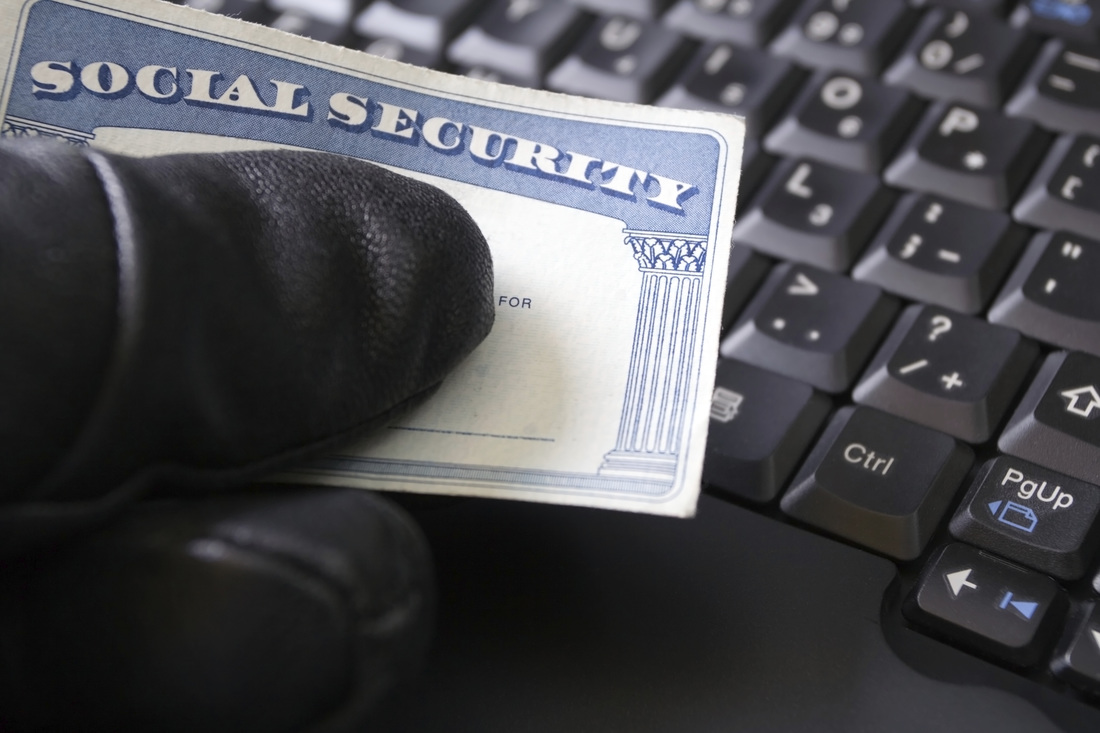 Picture of shady black glove holding social security card over computer, as if to imply the card is stolen