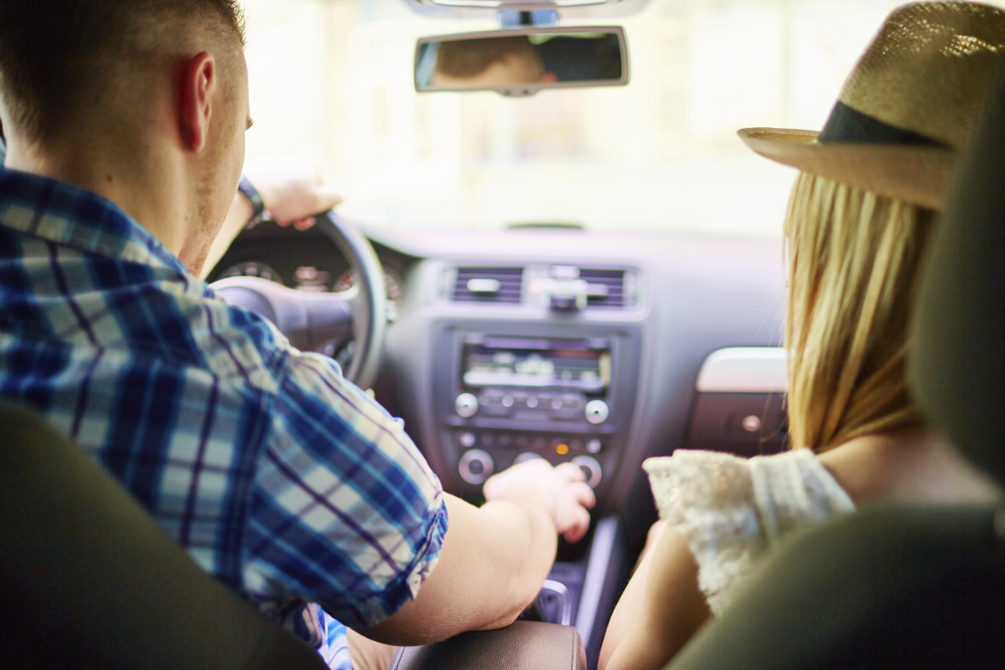 Picture of Young Couple in Front Seat of Car Playing with the Radio