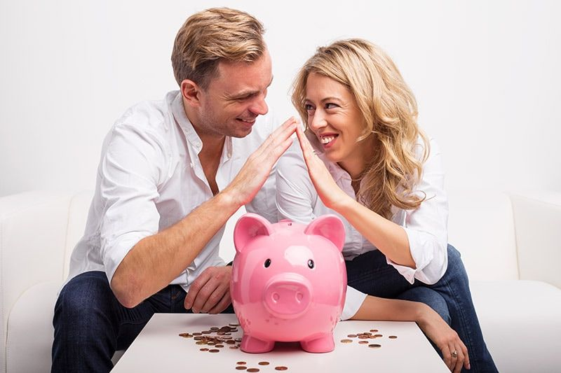 Married couple giving high five over a piggy bank